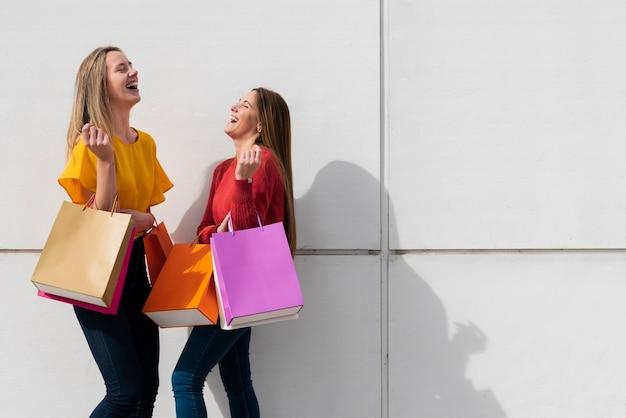 Chicas riendo con bolsas de compras Foto gratis