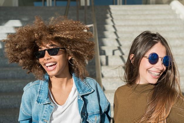 Chicas riendo juntas al aire libre Foto gratis
