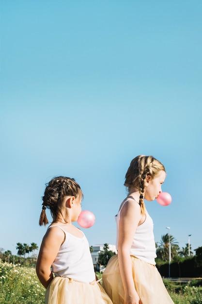 Chicas soplando chicles en el campo Foto gratis
