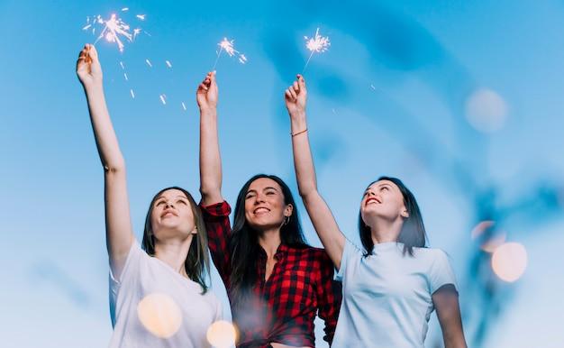 Chicas sosteniendo fuegos artificiales en la azotea al amanecer Foto gratis