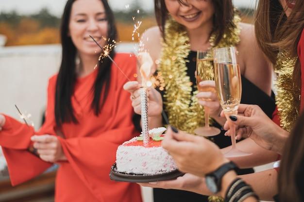 Chicas sosteniendo el pastel de cumpleaños y bengalas en una fiesta Foto gratis