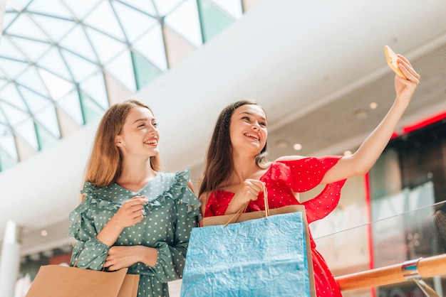 Chicas de tiro medio en el centro comercial tomando una selfie Foto gratis