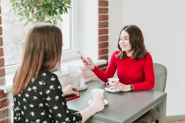 Chicas tomando café en un restaurante Foto gratis