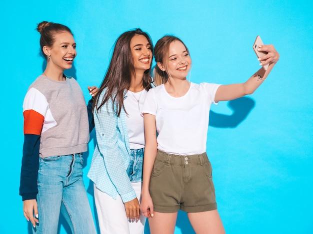 Chicas tomando fotos de autorretrato autofoto en smartphone.modelos posando cerca de la pared azul en el estudio, hembra mostrando emociones positivas Foto gratis