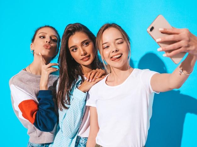 Chicas tomando fotos de autorretrato en el teléfono inteligente. modelos posando junto a la pared azul en el estudio. mujeres mostrando emociones positivas Foto gratis