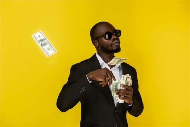 Chico afroamericano barbudo está arrojando dólares de una mano, con gafas de sol y traje negro Foto gratis