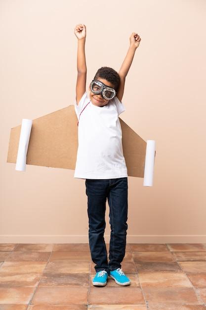 Chico afroamericano con sombrero de aviador y con alas Foto Premium