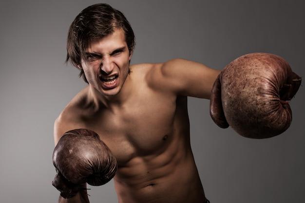 Chico agresivo en guantes de boxeo Foto gratis