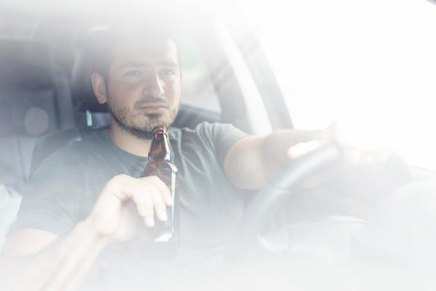 Chico con alcohol conduciendo coche Foto gratis