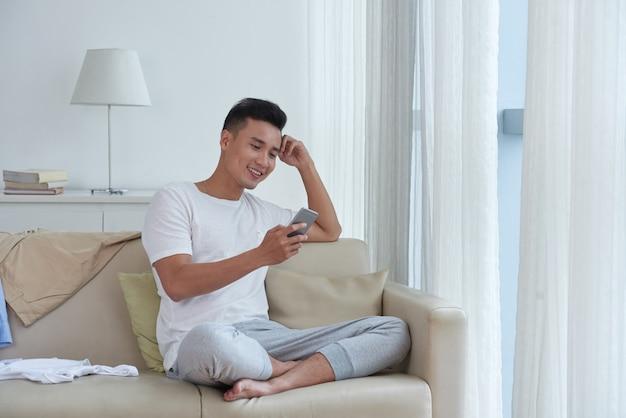 Chico alegre disfrutando de su tiempo libre mirando las redes sociales sentado cómodamente en el sofá Foto gratis