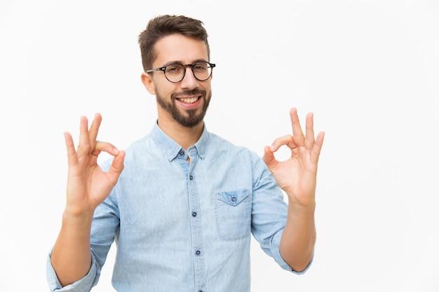 Chico alegre feliz mostrando gesto bien Foto gratis