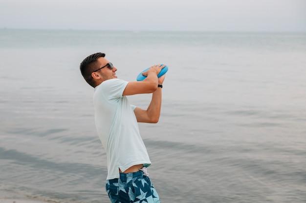 Chico alegre a punto de lanzar un disco frisbee, jugando cerca del mar. Foto gratis