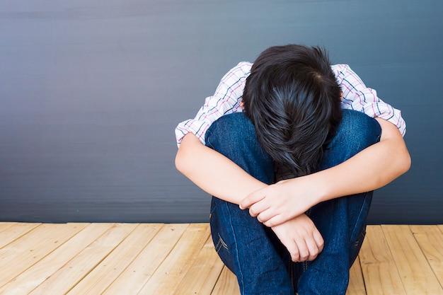 Un chico asiático de 7 años se siente triste. Foto gratis