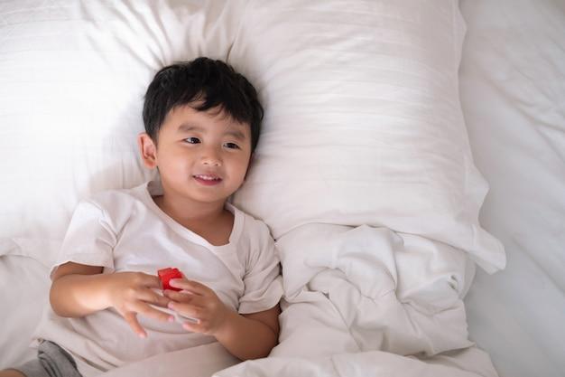 Chico asiático en casa en la cama Foto Premium