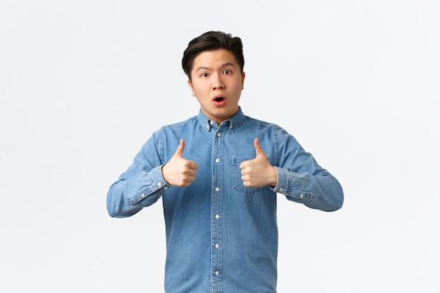 Chico asiático guapo impresionado y asombrado que muestra el pulgar hacia arriba y se ve asombrado, felicita a la persona con un trabajo excelente, buen trabajo inesperado, diciendo bien hecho, pared blanca Foto gratis