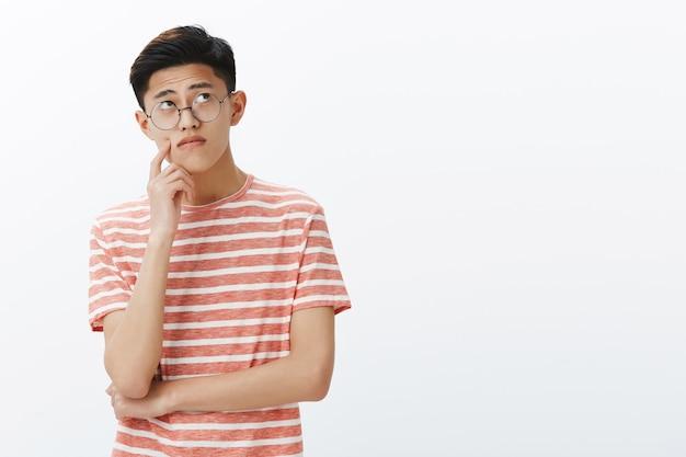 Chico asiático inteligente resolviendo acertijos en mente, mirando pensativo y relajado en la esquina superior derecha, pensando, haciendo suposiciones tocando la mejilla mientras hace un plan o una decisión Foto gratis
