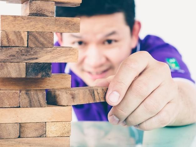 Un chico asiático está jugando un juego de torres de madera para practicar habilidades físicas y mentales. Foto gratis