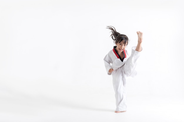 Chico asiático taekwondo pateando en estudio blanco Foto Premium