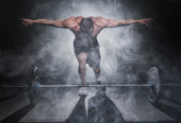 Chico atlético muy poderoso de pie con barra, entrenamiento en el gimnasio Foto Premium