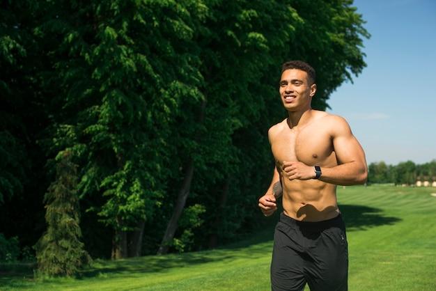 Chico atlético practicando deporte al aire libre Foto gratis