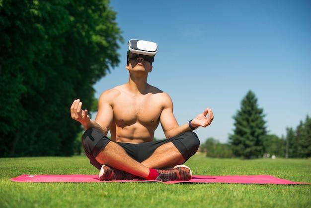 Chico atlético usando unas gafas de realidad virtual al aire libre Foto gratis