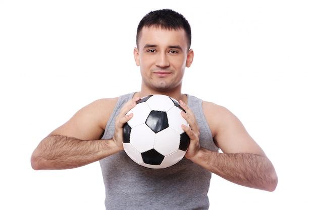 Chico atractivo con balón de fútbol Foto gratis
