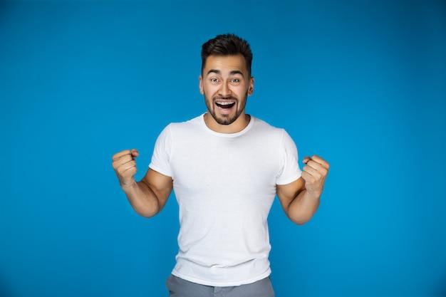 Chico atractivo feliz sobre el fondo azul Foto gratis