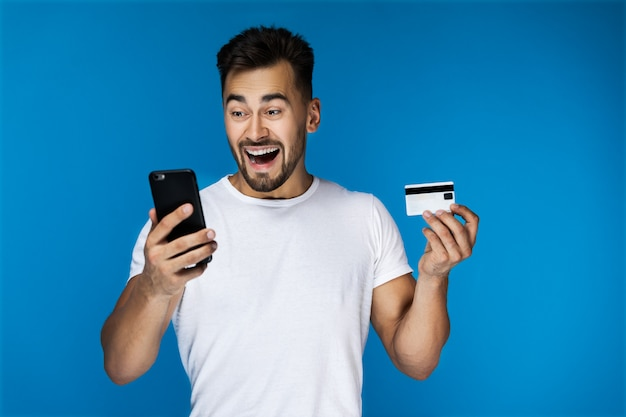 Chico atractivo sorprendido está mirando en el teléfono celular y con tarjeta de crédito Foto gratis