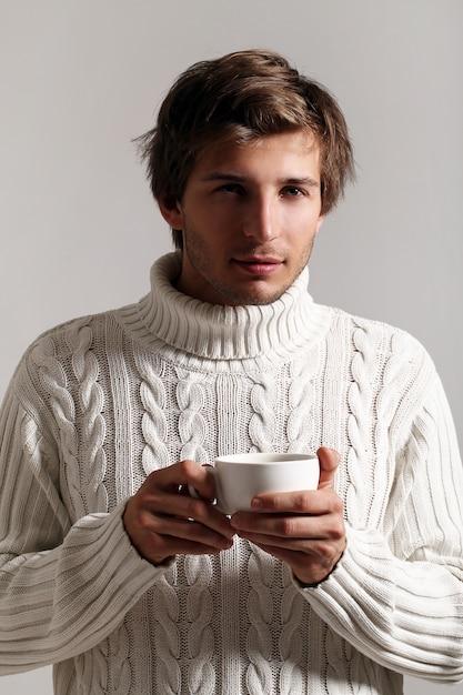 Chico atractivo sosteniendo una taza de café Foto gratis