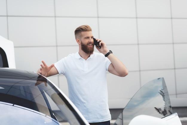 Chico con barba hablando por teléfono cerca de su auto eléctrico Foto Premium