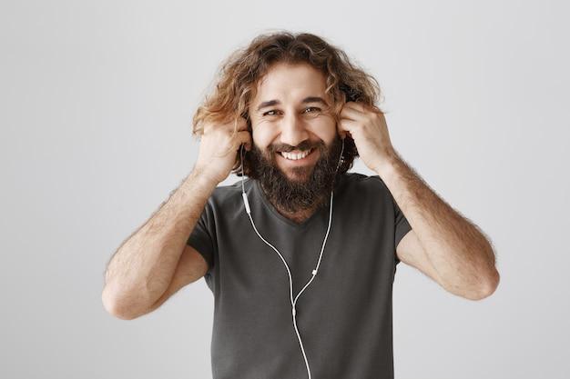 Chico barbudo alegre se puso los auriculares y sonriendo feliz, escuchando música Foto gratis