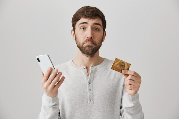 Chico barbudo molesto con tarjeta de crédito y smartphone Foto gratis