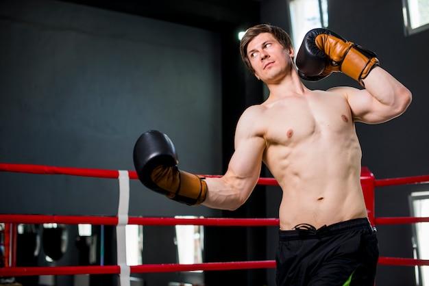 Chico boxeador posando en el gimnasio Foto gratis