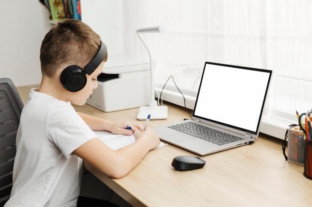 Chico a casa asistiendo a clases online Foto gratis