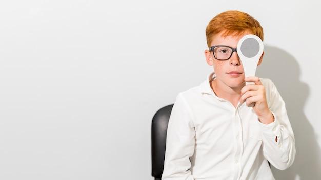 Chico caucásico con anteojos con oclusor delante de su ojo Foto gratis