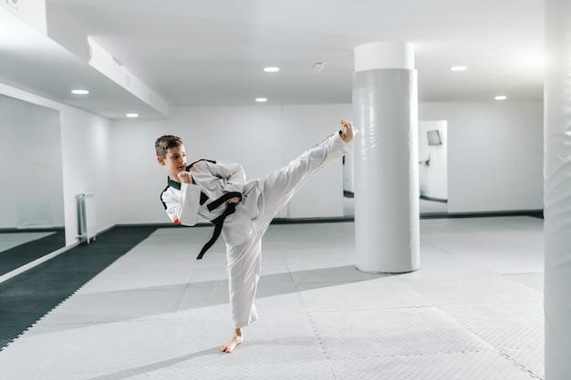 Chico caucásico en dobok pateando en pose de dollyo-chagi. concepto de entrenamiento de taekwondo. Foto Premium