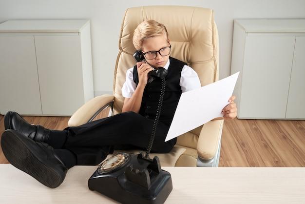 Chico caucásico sentado en la oficina en silla ejecutiva con los pies en el escritorio y hablando por teléfono Foto gratis