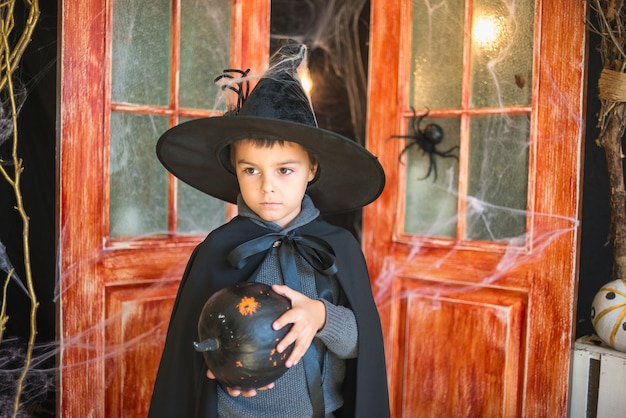 Chico caucásico en traje de mago de carnaval con calabaza pintada de negro sobre fondo de decoración de halloween Foto Premium