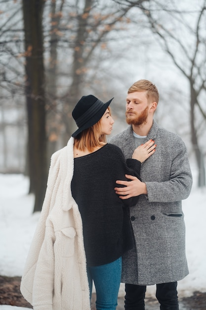 El chico y la chica descansan en el bosque de invierno. Foto gratis