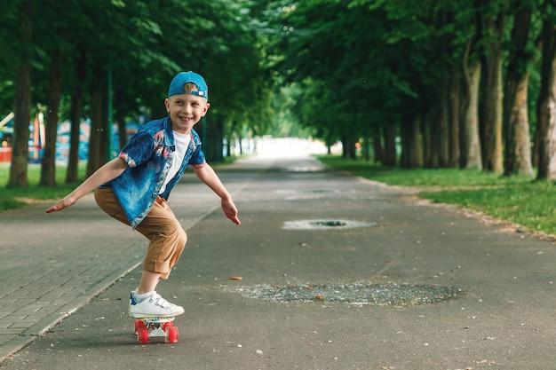 Un chico de ciudad pequeña y patineta. un chico joven está montando en una patineta parka Foto Premium