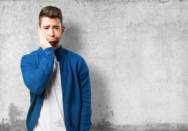 Chico con chaqueta azul con dolor de muelas Foto Gratis