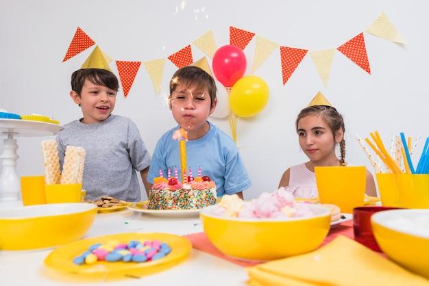 Chico de cumpleaños soplando velas con sus amigos Foto gratis