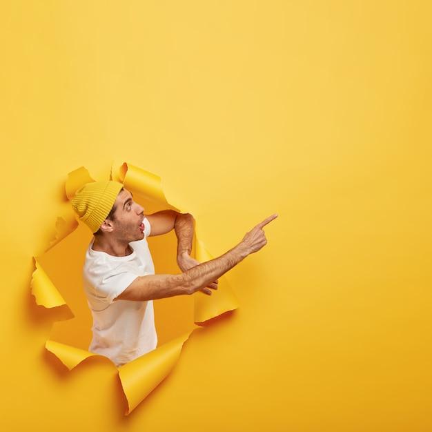 Chico emocionalmente sorprendido se encuentra en un agujero de papel con bordes amarillos rasgados, demuestra un increíble espacio de copia Foto gratis