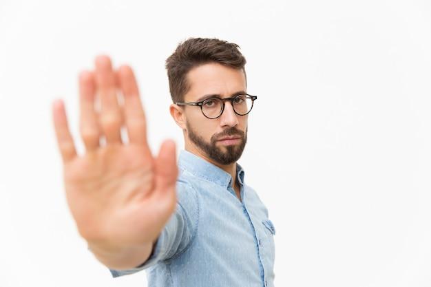 Chico estricto serio haciendo gesto de parada de mano Foto gratis