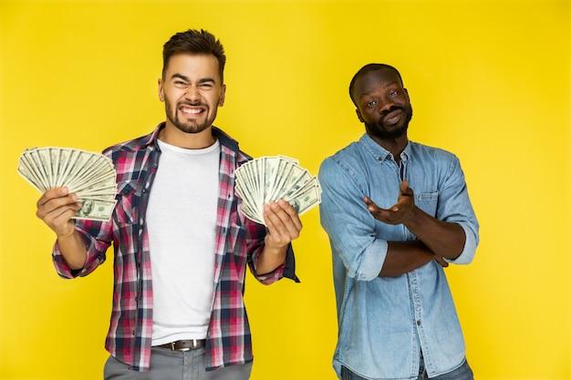 Un chico europeo con una gran cantidad de dinero en ambas manos y un chico afroamericano no tiene nada Foto gratis