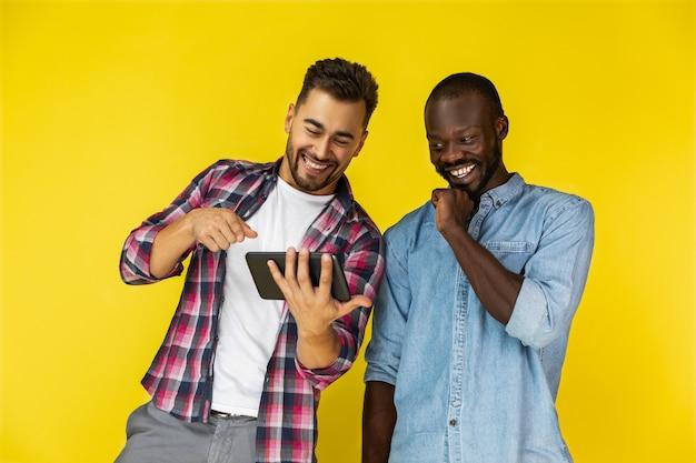 Un chico europeo está mostrando algo en la tableta y se está riendo junto con un chico afroamericano Foto gratis