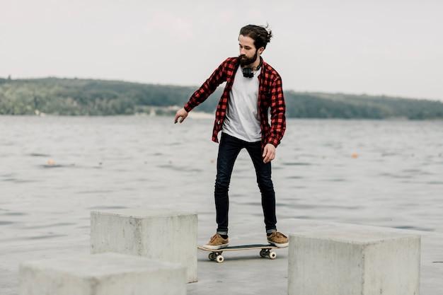 Chico en franela en patineta por un lago Foto gratis