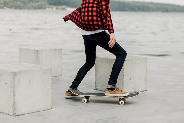 Chico en franela skate en el lago Foto gratis