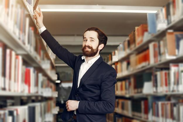 Chico guapo estudia en la biblioteca Foto gratis