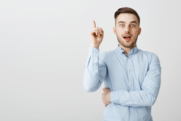 Chico guapo inteligente encontró una solución, levantando el dedo índice en gesto eureka Foto gratis